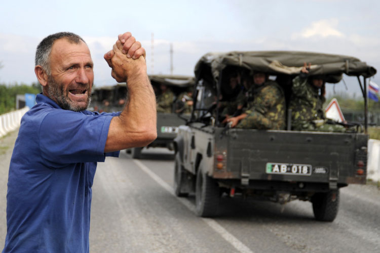A local resident greets Georgian troops moving into the city of Tskhinvali, 100 km (62 miles) from Tbilisi, August 8, 2008. Georgian troops, backed by warplanes, pounded separatist forces on the outskirts of the South Ossetian capital on Friday hours after launching an assault on the breakaway region following a short-lived truce. REUTERS/Irakli Gedenedze (GEORGIA)