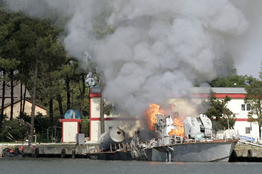 A Georgian navy ship burns in the Black Sea port of Poti August 13, 2008. REUTERS/Umit Bektas (TURKEY)